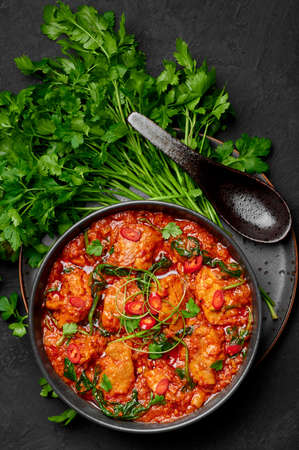 Chicken Vindaloo with spinach in black bowl on dark slate table top. Indian cuisine meat chilli curry dish. Authentic asian food. Top view