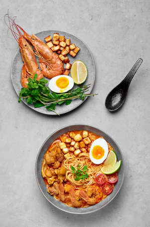 Laksa in gray bowl on concrete table top. Coconut noodle soup with chicken meat and prawns of peranakan cuisine. Asian food.