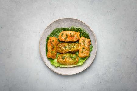 Golubtsi or golabki on gray plate on concrete table top. Stuffed cabbage rolls dish of russian, polish, ukrainian cuisine. European food.
