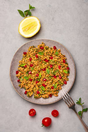 Kisir on gray plate on concrete table top. Turkish cuisine bulgur and parsley salad dish with pomegranate. Turkish food and meal. Top view. Banque d'images