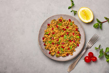 Kisir on gray plate on concrete table top. Turkish cuisine bulgur and parsley salad dish with pomegranate. Turkish food and meal. Top view. Copy space