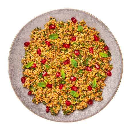 Kisir on gray plate isolated on white. Turkish cuisine bulgur and parsley salad dish with pomegranate. Turkish food and meal.