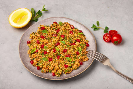 Kisir on gray plate on concrete table top. Turkish cuisine bulgur and parsley salad dish with pomegranate. Turkish food and meal.