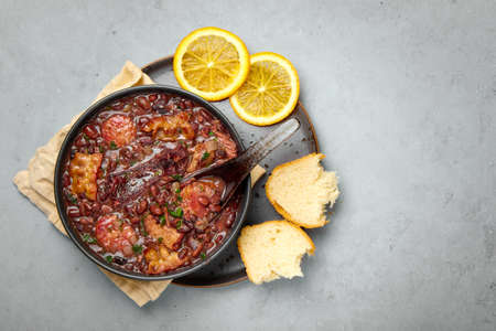 Feijoada in black bowl gray concrete table top. Brazilian and portuguese cuisines traditional beans meat stew