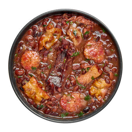 Feijoada in black bowl isolated on white. Brazilian and portuguese cuisines traditional beans meat stew