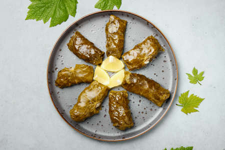 Dolma or sarma on black plate on gray concrete table top. Turkish, greek or georgian cuisines dish with stuffed grape leaves. Top view