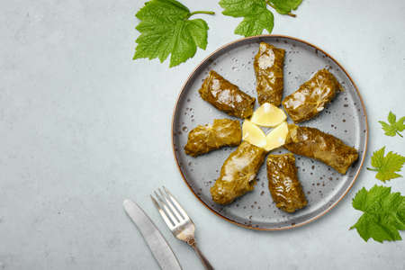 Dolma or sarma on black plate on gray concrete table top. Turkish, greek or georgian cuisines dish with stuffed grape leaves. Top view. Copy space Banque d'images