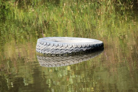 Tire carelessly thrown away in the nature  Carelessly discarded items pollute the environment and cause problems for all humanity