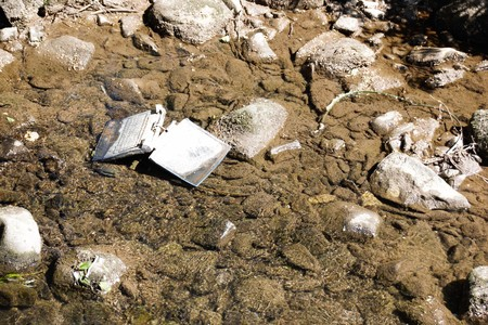 Laptop in the river  Carelessly discarded items pollute the environment and cause problems for all humanity