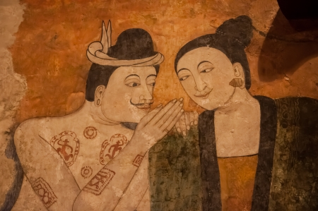 Ancient Buddhist temple mural depicting a Thai daily life scene at Wat Phumin, a famous temple in Nan province, Thailand. The temple is open to the public and has beautiful murals on the walls.