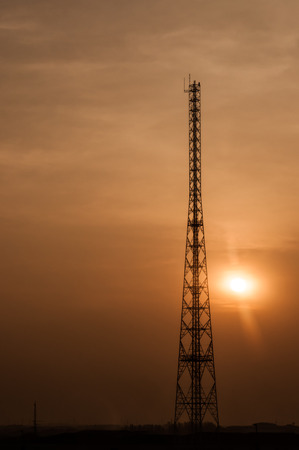 Silhouette of telecommunications tower on dramatic sunset sky photo