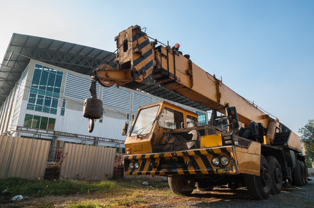 maneuverable: yellow automobile crane with risen telescopic boom outdoors over blue sky