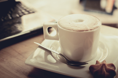 evaporating: laptop and cup of hot evaporating coffee on table, filtered image Stock Photo