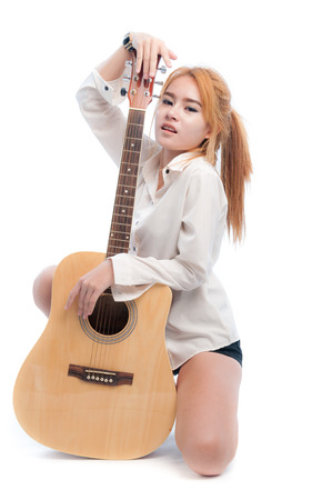 Glamorous young woman in white shirt with her guitar on a white background photo