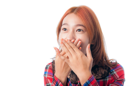 Surprised young woman covering her mouth with hands on white background photo
