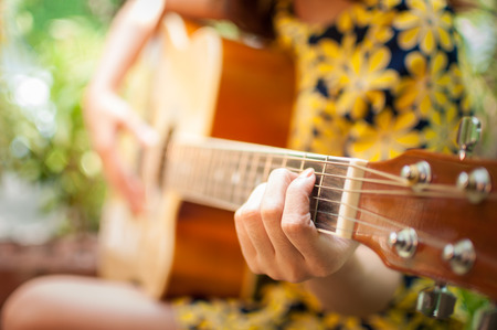 Closeup of young womans hands playing acoustic guitar outdoors photo