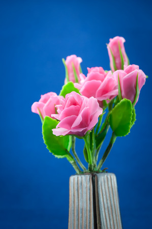 Artificial Flowers made of japanese clay on blue blackground photo