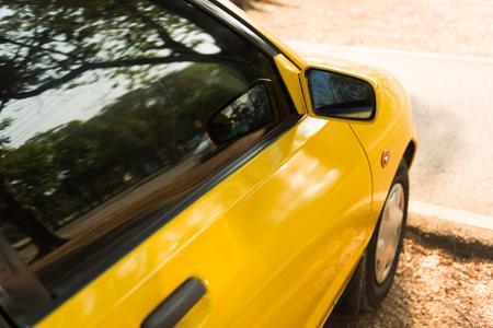 rear view mirror: Rear view mirror of yellow car Stock Photo