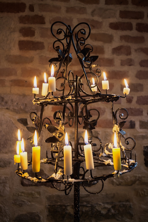 Historical candlestick with a burning wax candles in front of a brick wall Catholic church basement.