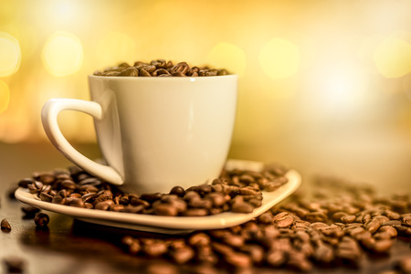 cup full of coffee beans on a wooden table, blurred background