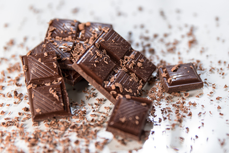 Chocolate. Black chocolate. A few cubes of black chocolate. Chocolate slabs spilled from grated chockolate powder.nuts