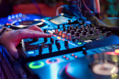 Professional sound mixer for musical events. hands of the DJ operator in the background colorful light atmosphere