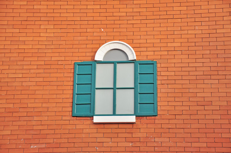 Window with shutters on brick wall.