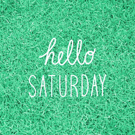 saturday: Hello Saturday greeting on green grass background. Stock Photo