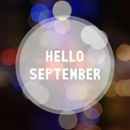 in september: Hello September lettering on bokeh background. Stock Photo
