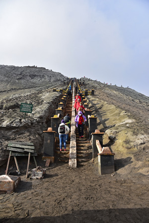 EAST JAVA, INDONESIA - OCT 19, 2015: Tourists climbing the stairway leading to the rim of Mount Bromo in East Java, Indonesia.