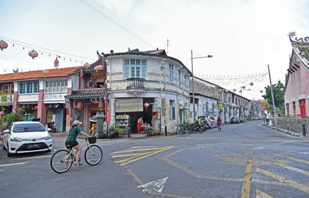 GEORGE TOWN, PENANG, MALAYSIA - JULY 30, 2015 : Unidentified woman riding bicycle in George Town, Penang, Malaysia. Editorial