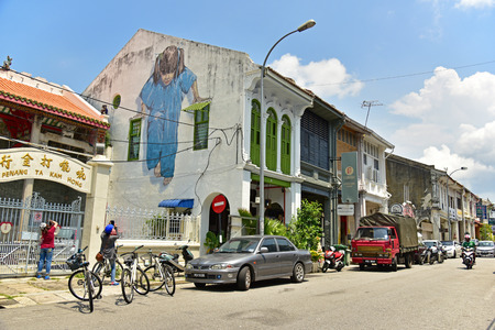 wall mural: GEORGETOWN PENANG, MALAYSIA - JULY 30, 2015: Tourists are taking photos Little Girl in Blue Painted wall mural by artist Ernest Zacharevic in George Town, Penang, Malaysia. Editorial