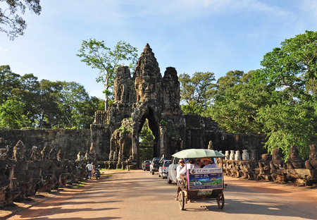 SIEM REAP, CAMBODIA - AUGUST 10: Tourists visit South gate of Angkor Thom on August 10, 2014 in Siem Reap, Cambodia.