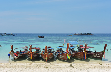 LIPE - SATUN, THAILAND - MARCH 1, 2016: Long tail wooden boats on the beach for tourists around Lipe island, Andaman sea in Satun, Thailand. Editorial
