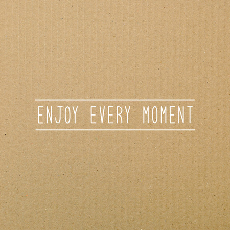 Enjoy every moment. Inspirational quote on brown paper. Stock Photo