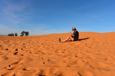 ne: Tourist in red sand dunes, Mui Ne, Vietnam. Stock Photo