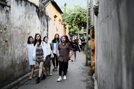 HOI AN, VIETNAM - NOVEMBER 24, 2016: Tourists visit Hoi An ancient town. Hoi An is a popular tourist destination of Asia. Hoi An is recognized as a World Heritage Site by UNESCO.