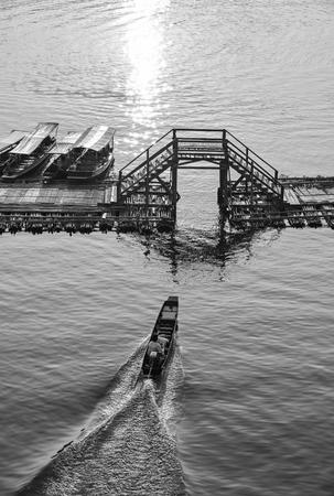 SANGKHLABURI-KANCHANABURI, THAILAND - MARCH 30 A traditional long tail boat sailing with the driver on the river in the morning on March 30, 2015 in Sangkhlaburi, Kanchanaburi, Thailand.