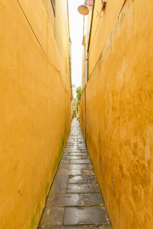 Path between yellow buildings at Hoi An ancient town.