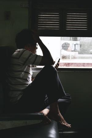KANCHANABURI, THAILAND - MAR 29, 2015 : Old man traveling by the train sitting near the window in Kanchanaburi, Thailand. Vintage tone.