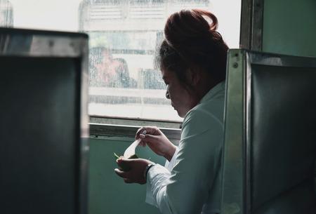 KANCHANABURI, THAILAND - MAR 29, 2015 : Woman traveling by the train eating near the window in Kanchanaburi, Thailand. Vintage tone.