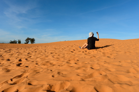 ne: Woman tourist taking photos in red sand dunes, Mui Ne, Vietnam.