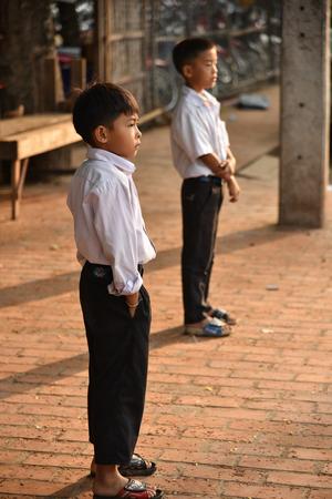 LUANG PRABANG, LAOS - MAY 04 Unidentified boys and girl waiting to go to school on May 04, 2015 in Luang Prabang, Laos.