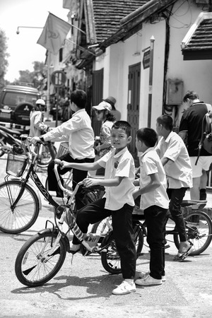 LUANG PRABANG, LAOS - MAY 05, 2015 : Unidentified boys on the road in downtown Luang Prabang. It was the royal capital of the Kingdom of Laos and selected as World Heritage Site. Black and white. Editorial