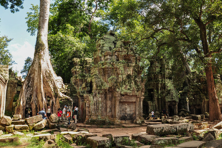 SIEM REAP, CAMBODIA - AUGUST 10: Unidentified tourists visit Ta Prohm temple on August 10, 2014 in Siem Reap, Cambodia.