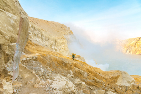 KAWAH IJEN, INDONESIA - OCT 18, 2015 : Worker carries sulfur (sulphur) inside Ijen crater in Ijen Volcano, Indonesia. Miners are extracting gaseous sulfur going out in the mine of the crater.