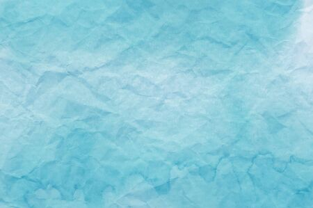 Blue watercolor on crumpled paper useful as a background.