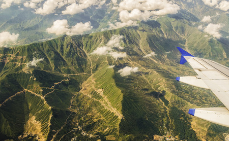treacherous: Aerial view of the green vegetation covered great Himalayas from the plane. Visible are the treacherous roads and the floating cumulus clouds.