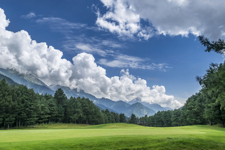 of course: Pahalgam Golf Course is a 18 hole course, surrounded by snow capped mountains, pine trees, lush green grass and the perfect blue sky with white clouds. Stock Photo