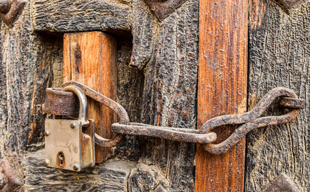 old styled: Old styled rusty chain door lock on the wooden door of a house in Jaisalmer, Rajasthan, India Stock Photo